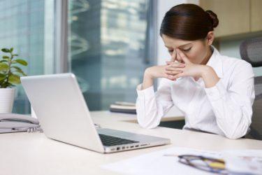 девушка за компьютером держится за глаза