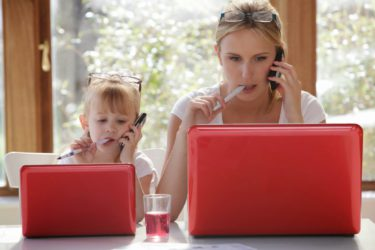 мама и дочка сидят за компьютерами в одинаковых позах