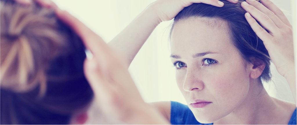 девушка смотрит на волосы в зеркало