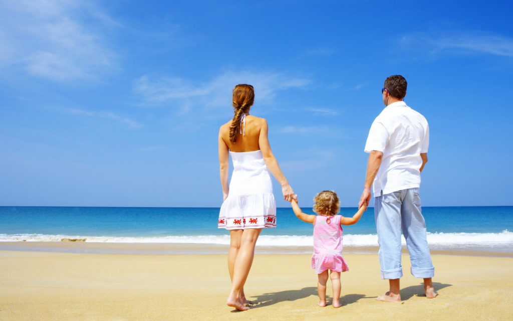 родители с девочкой идут по берегу моря