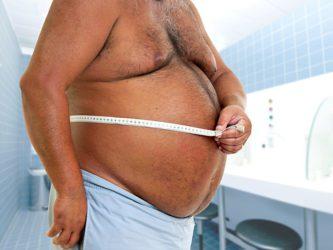 мужчина измеряет живот
