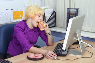 Девушка за компьютером ест бутерброд