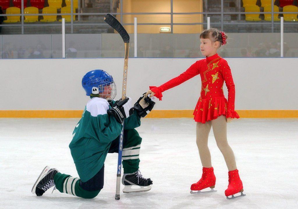 Хоккеист-мальчик на колене перед девочкой-фигуристкой