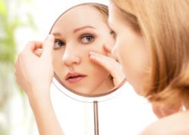 девушка смотрит на свое лицо в зеркало